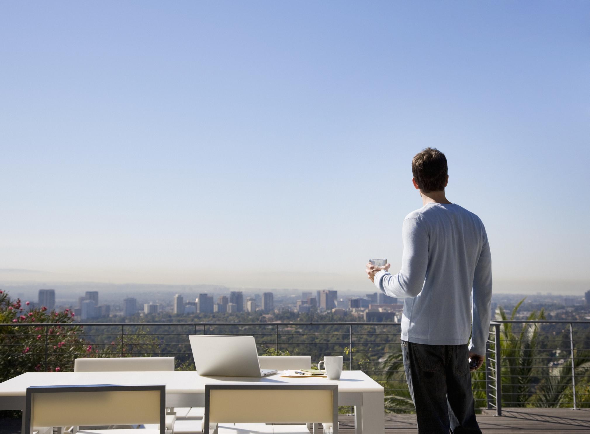 man-using-laptop-on-balcony-overlooking-cityjpg