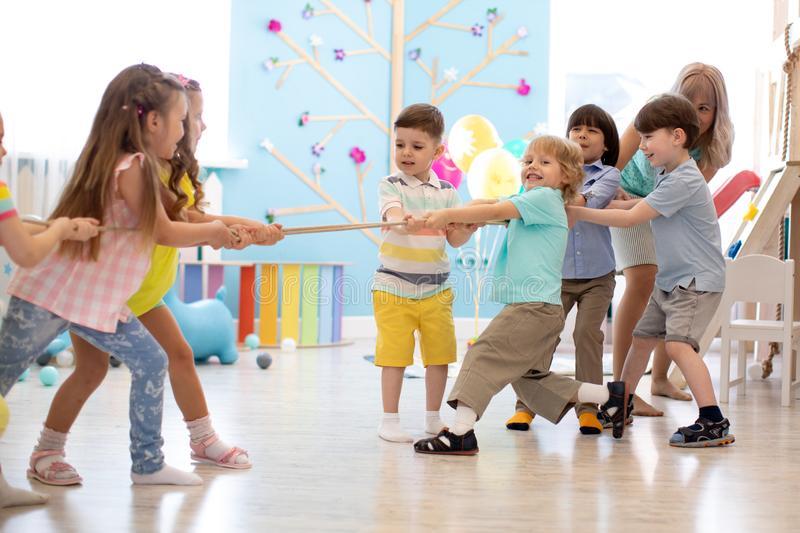 grupa-dzieciaki-i-ci-gnienie-arkana-bawi-si-wp-lnie-w-daycare-preschool-artuje-sztuki-gnienia-arkan-148058584jpg